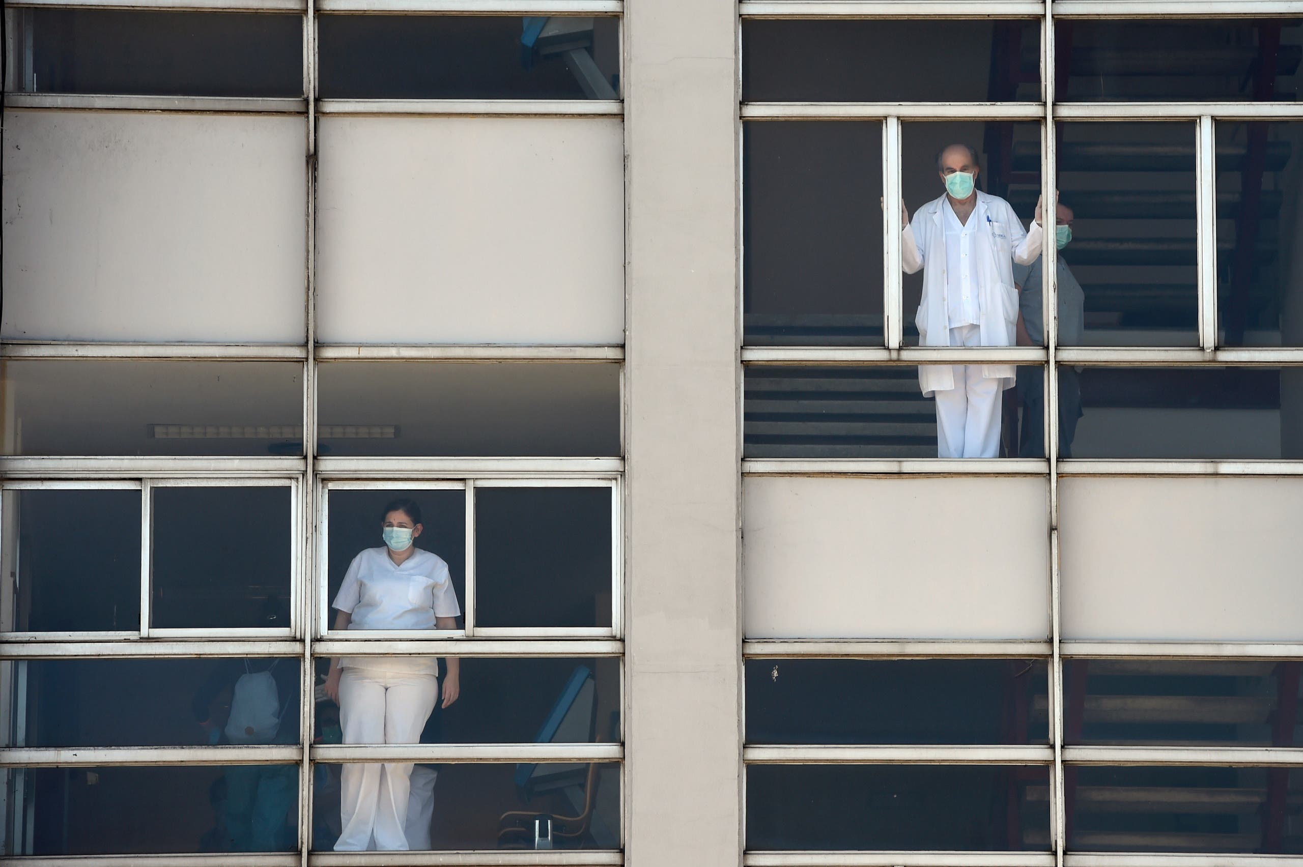 Healthcare workers dealing with the new coronavirus crisis look through the windows of the University Hospital in Coruna, northwestern Spain, on March 26, 2020. (AFP)