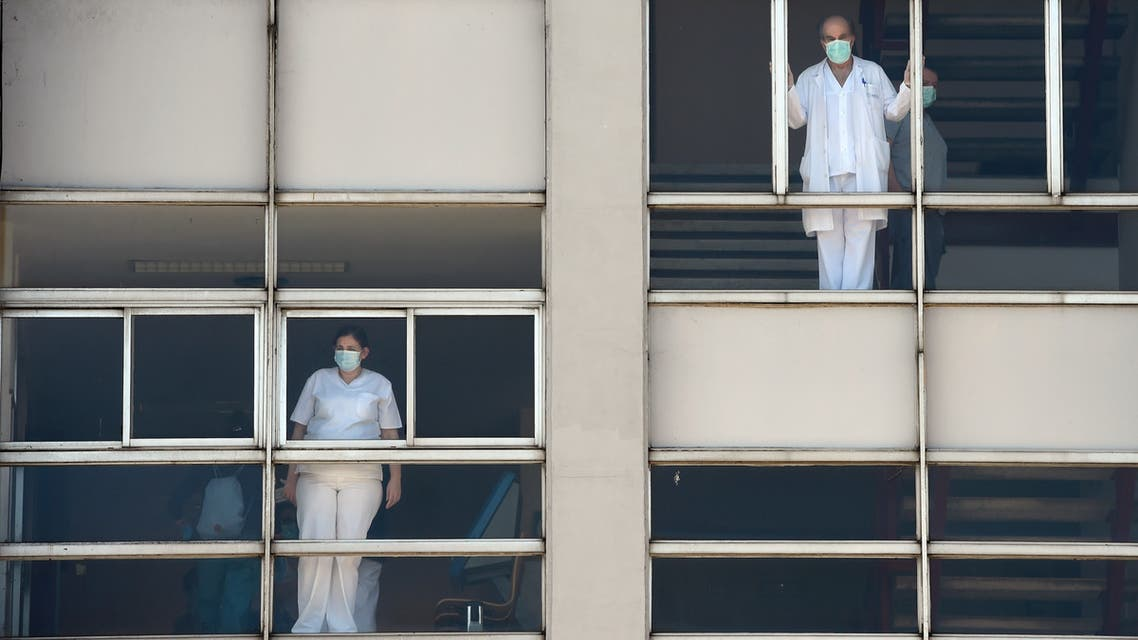 Healthcare workers dealing with the new coronavirus crisis look through the windows of the University Hospital in Coruna, northwestern Spain, on March 26, 2020. Spain's coronavirus death toll surged above 4,000 today but the increase in both fatalities and new infections slowed, leaving officials hopeful a nationwide lockdown is starting to curb the spread of the disease. A total of 655 deaths were recorded in the country in the last 24 hours, bringing the toll to 4,089, the health ministry said.