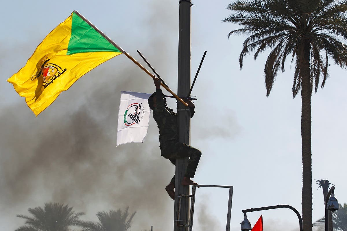 A member of Hashd al-Shaabi holds a flag of Kataib Hezbollah militia group during a protest to condemn air strikes on their bases, in Baghdad. (File photo: Reuters)