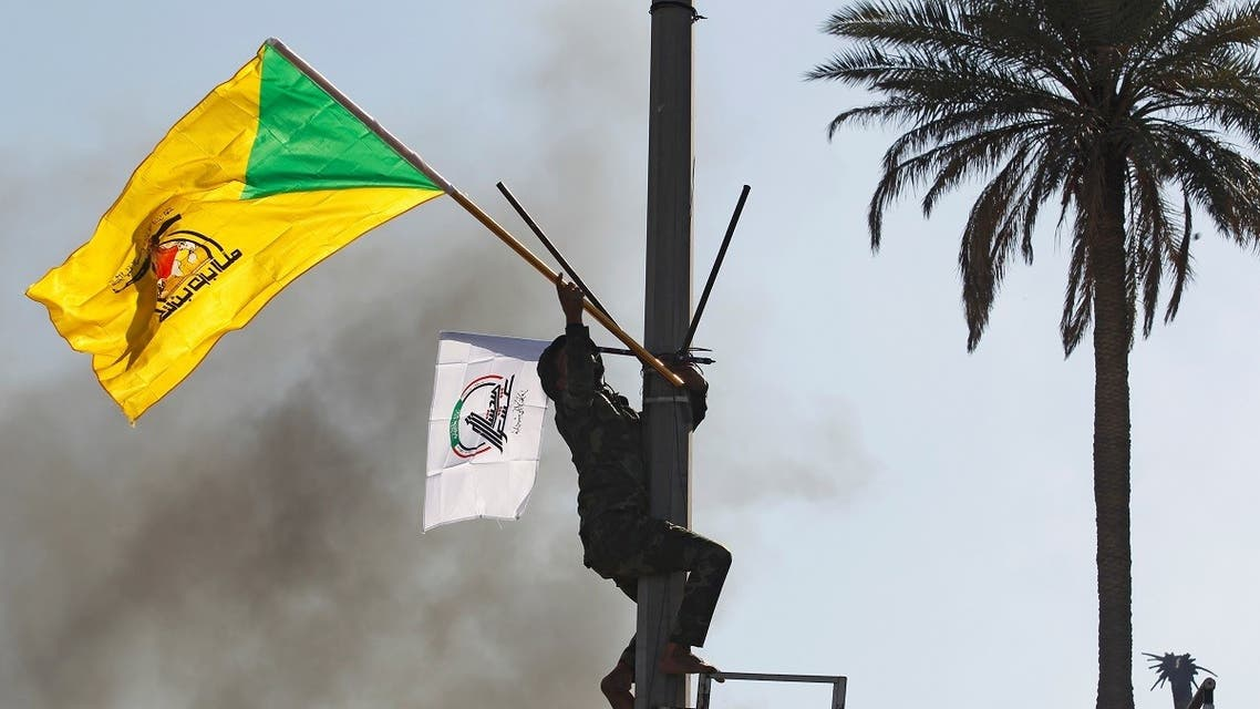 A member of Hashd al-Shaabi holds a flag of Kataib Hezbollah militia group during a protest to condemn air strikes on their bases, in Baghdad. (Reuters)