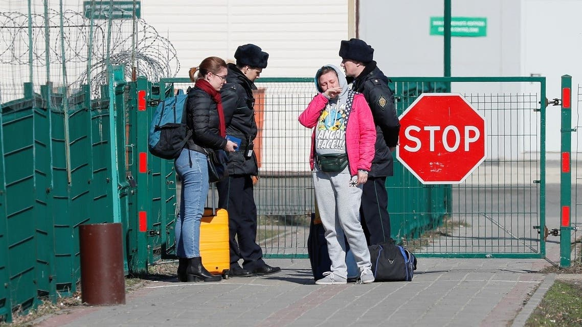 Ukrainian citizens react near Russian border guards at a crossing point in Hoptivka. (File photo: Reuters)