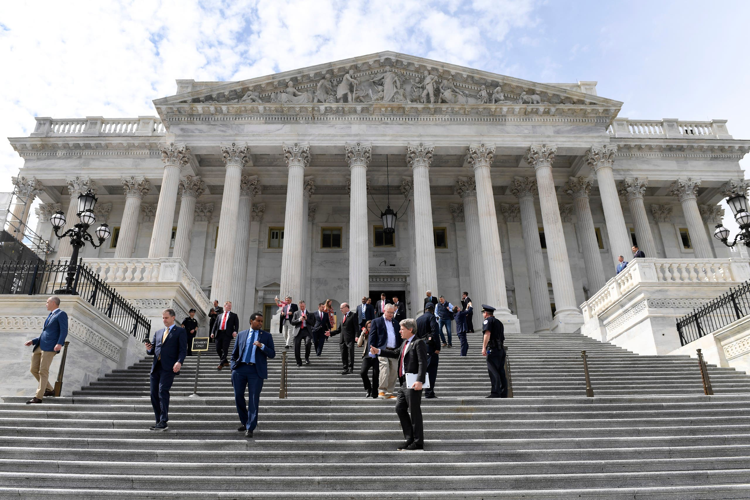 Members of the House of Representatives walk down the steps of Capitol Hill in Washington, on March 27, 2020, after passing a coronavirus rescue package. (AP)