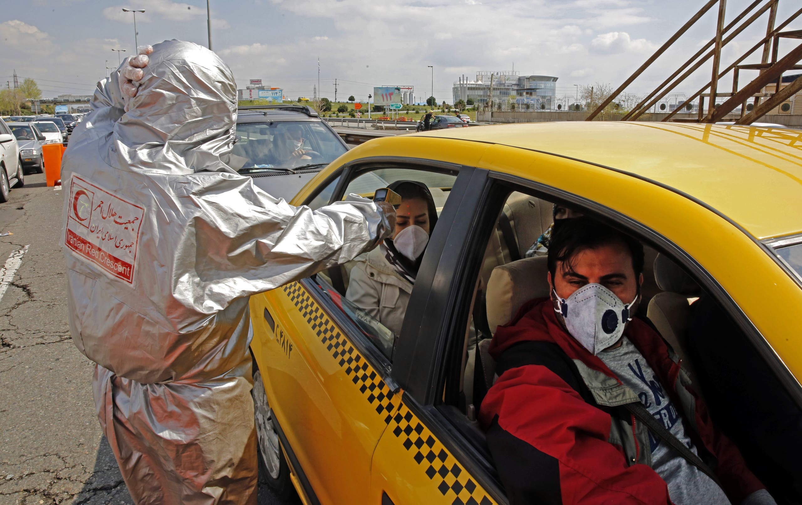 Members of the Iranian Red Crescent test people for coronavirus outside Tehran on March 26, 2020. (AFP)