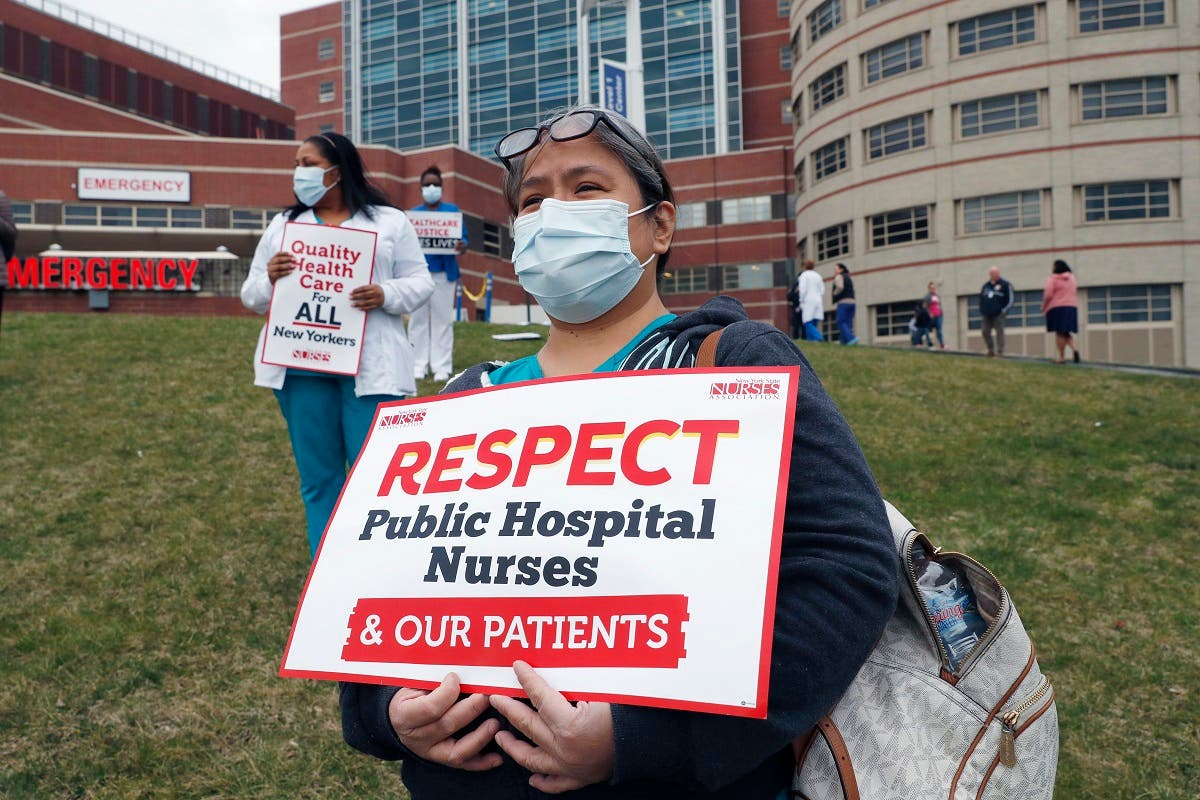 Nurses stand outside the emergency entrance to Jacobi Medical Center in the Bronx borough of New York, on March 28, 2020, demanding adequate supply of personal protective equipment. (AP)