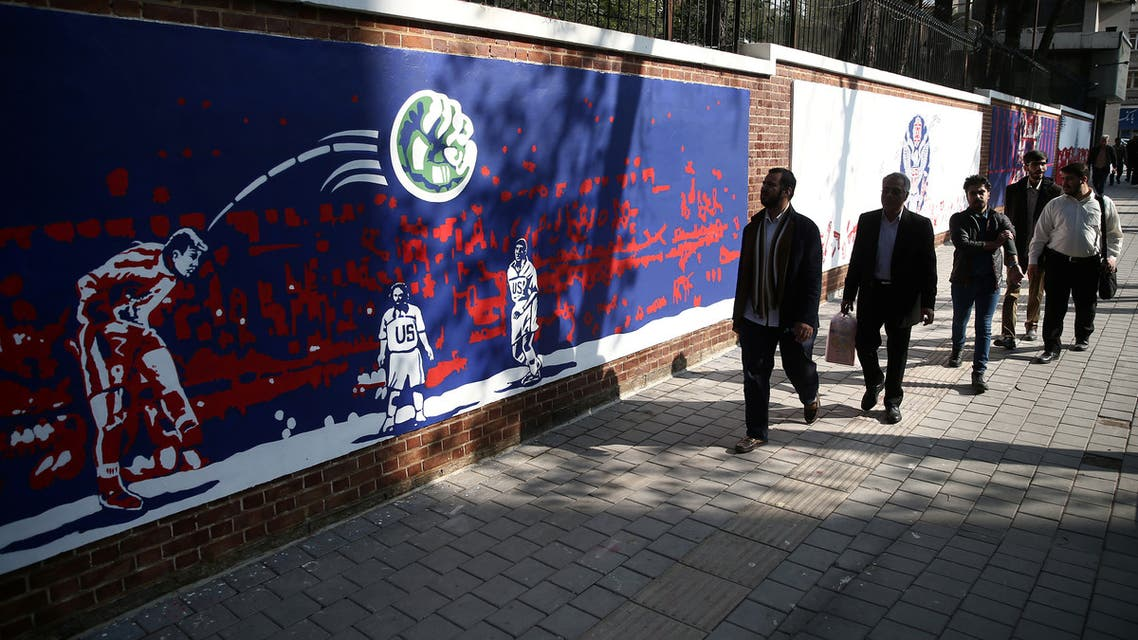 People walk in front of new murals of the former US embassy in Tehran, Iran. (Reuters)