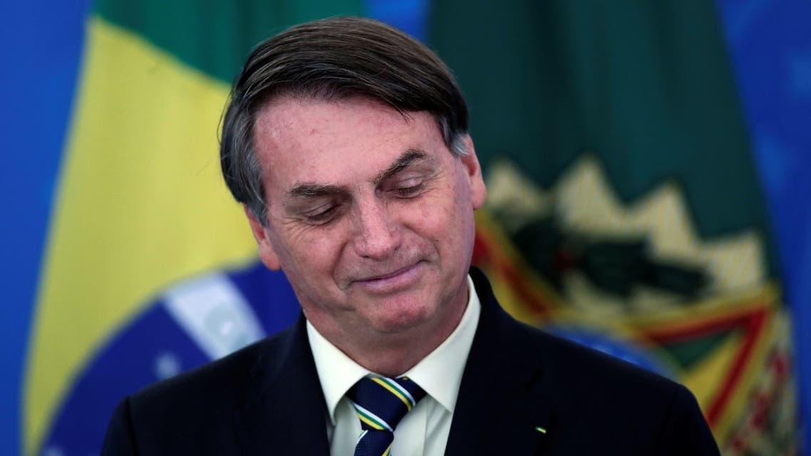 Brazil's President Jair Bolsonaro smiles at a media statement announcing economic measures during the coronavirus disease (COVID-19) outbreak in Brasilia, Brazil, March 27, 2020. (Reuters)