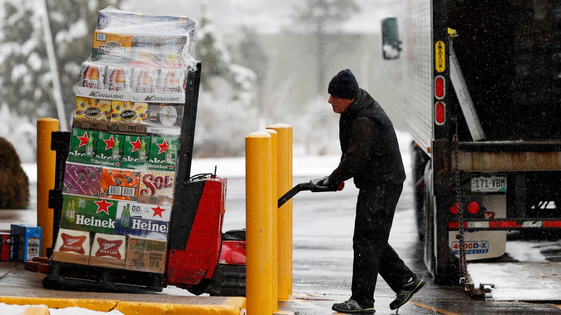 A delivery truck driver guides a large order of beer into a liquor store as shoppers empty the shelves during the closing of bars and restaurants because of the spread of coronavirus on March 19, 2020, in Littleton, Colorado. (AP)