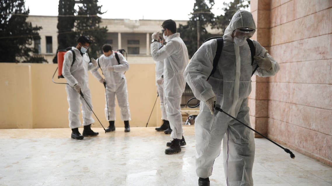 Members of a humanitarian aid agency disinfect Ibn Sina hospital as prevention against coronavirus in the city of Idlib, Syria, on March 19, 2020. (AP)