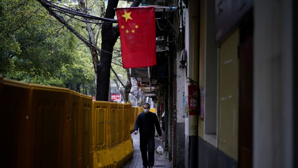 A man wearing a face mask walks next to barriers, which have been built to block buildings from a street in Wuhan, Hubei province, China, March 29, 2020. (Reuters)