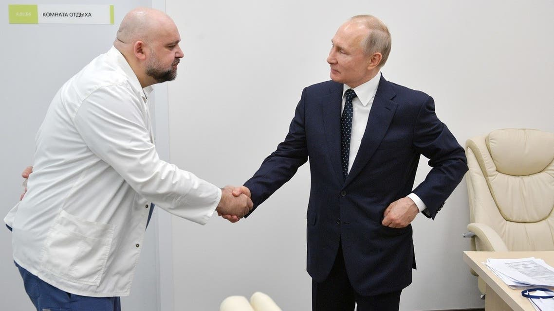 A picture taken on March 24, 2020 shows Russian President Vladimir Putin (R) shaking hands with the head of Moscow's new hospital treating coronavirus (COVID-19) patients Denis Protsenko. (AFP)