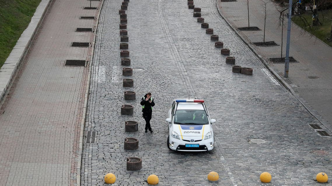 A police officer smokes in an empty street while patrolling central Kiev, Ukraine March 31, 2020. (Reuters)