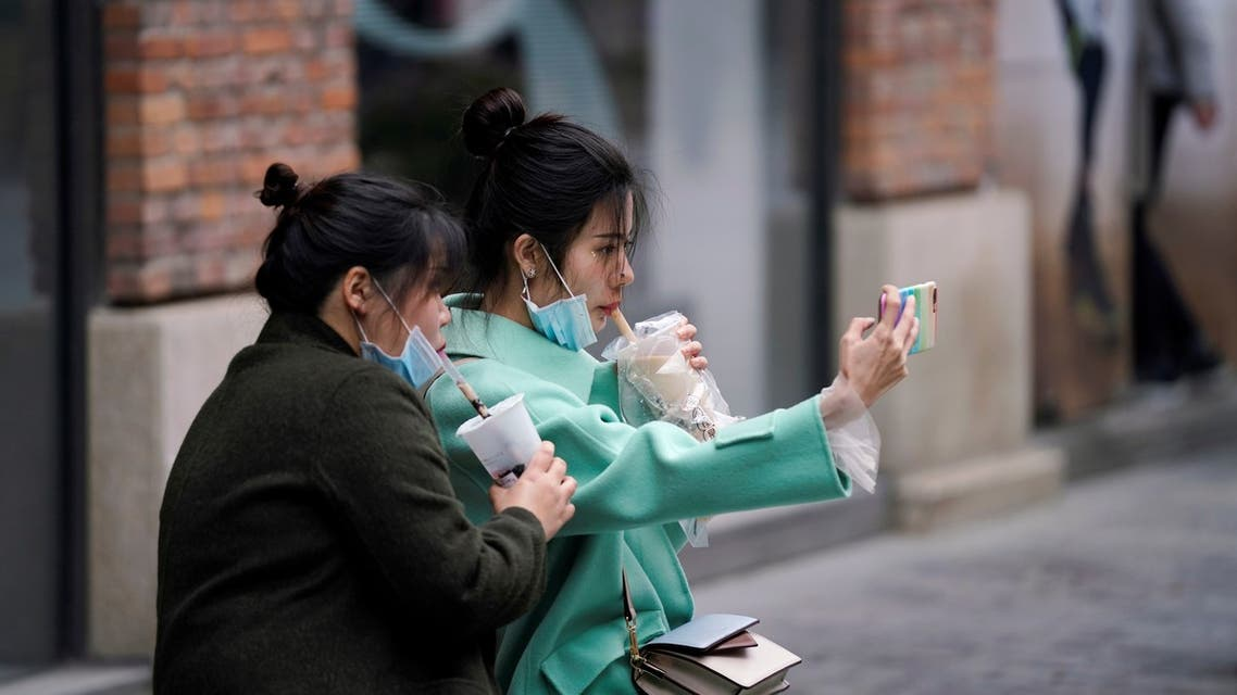 Women with face masks enjoy their bubble tea at a shopping complex in Wuhan, Hubei province, the epicentre of China's coronavirus disease (COVID-19) outbreak, March 31, 2020. REUTERS/Aly Song