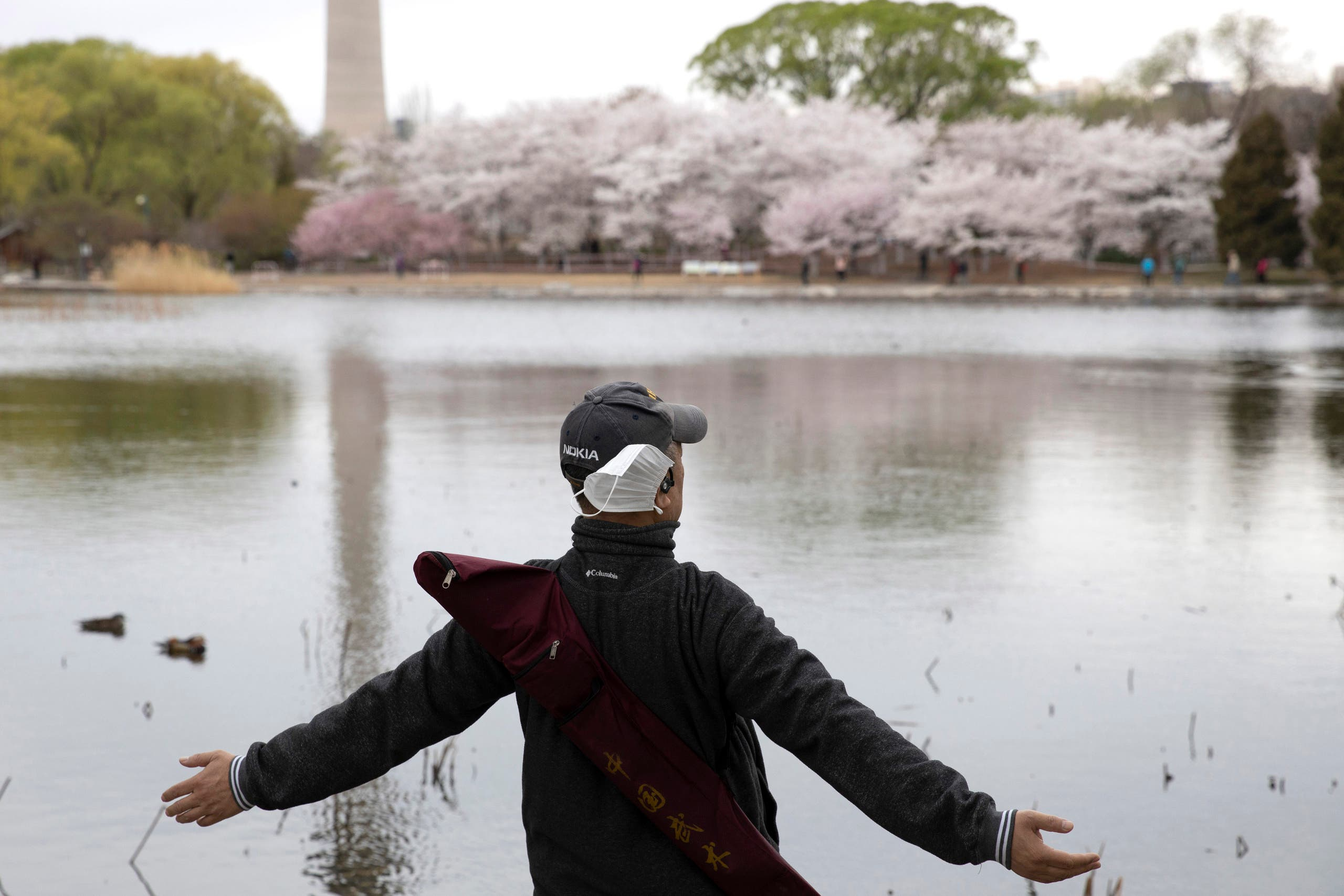 A man removes his mask to stretch and take a deep breath across from cherry blossoms at the Yuyuantan Park in Beijing on March 26, 2020. (AP)