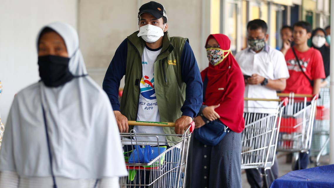Consumers wearing protective face masks line up in front of a market amid the coronavirus disease (COVID-19) outbreak in Jakarta, Indonesia March 30, 2020. REUTERS/Ajeng Dinar Ulfiana