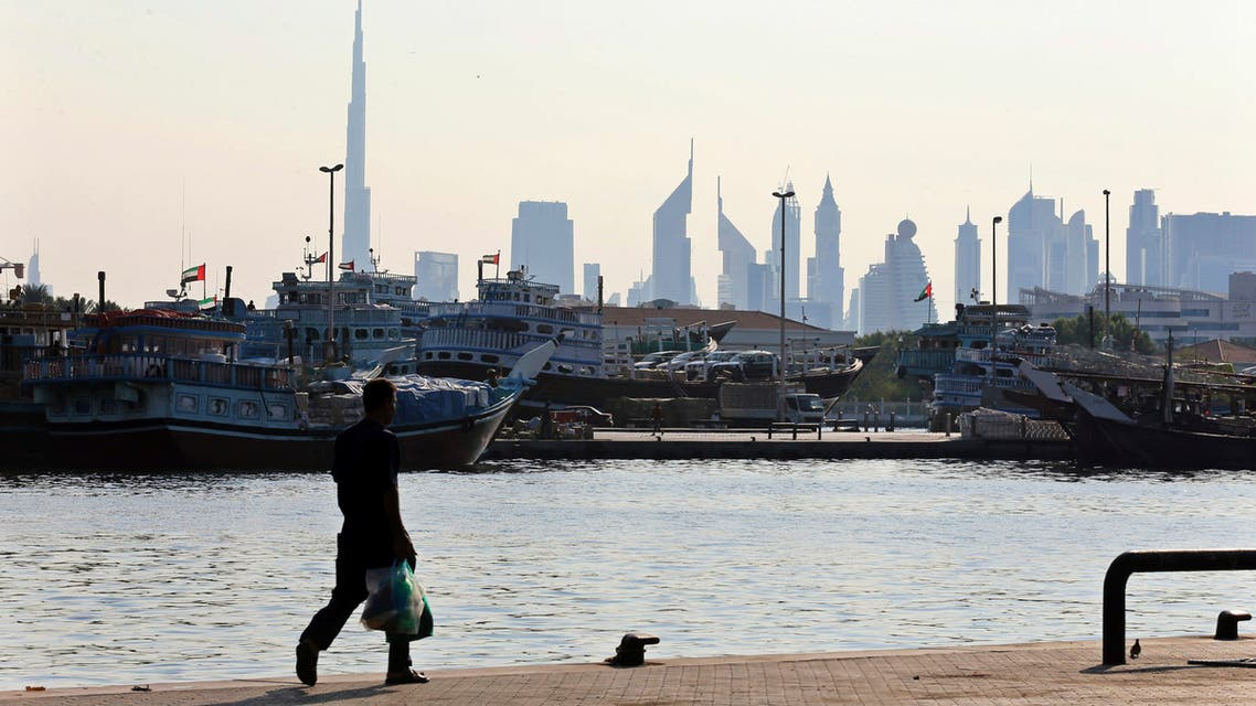A man walks at Dubai creek where ships loaded with goods, in Dubai November 24, 2013. (Reuters)