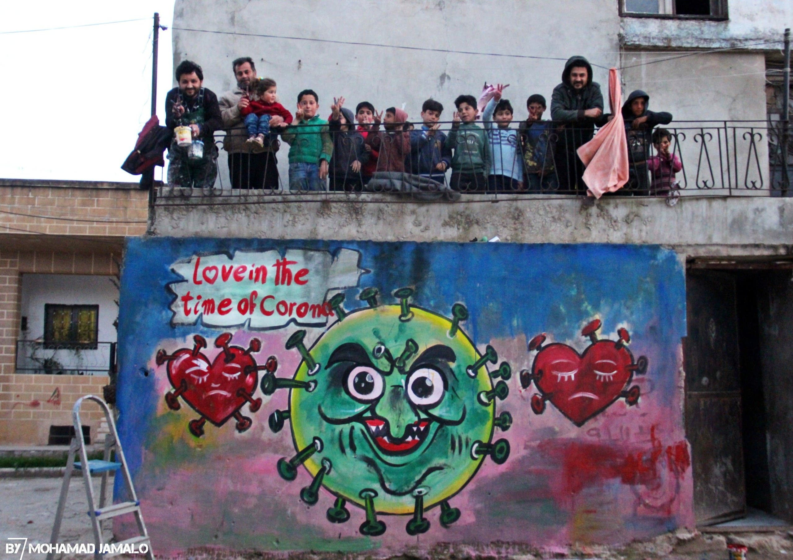 Syrian artist Aziz Asmar with children in Idlid above one of his coronavirus murals. (Mohamad Jamalo)