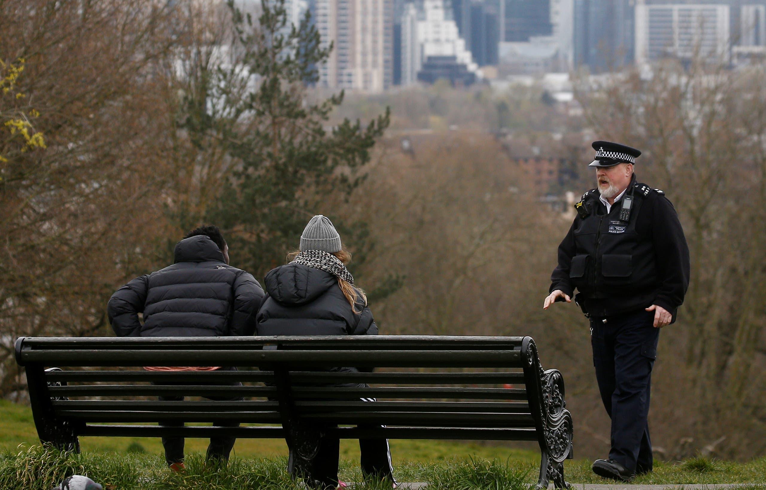 شرطي يؤنب اثنين يجلسان في حديقة عامة في لندن