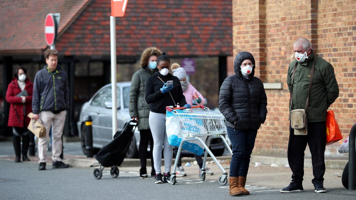 People wearing protective facemasks queue outside Sainsbury's supermarket in Streatham, as the spread of the coronavirus disease (COVID-19) continues, London, Britain, March 29, 2020. (Reuters)