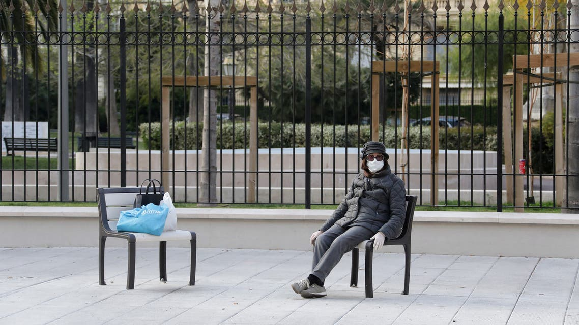 A woman wearing a protective face mask sits in a deserted street in Nice , as a lockdown is imposed to slow the rate of the coronavirus disease (COVID-19) in France, March 28, 2020. REUTERS/Eric Gaillard