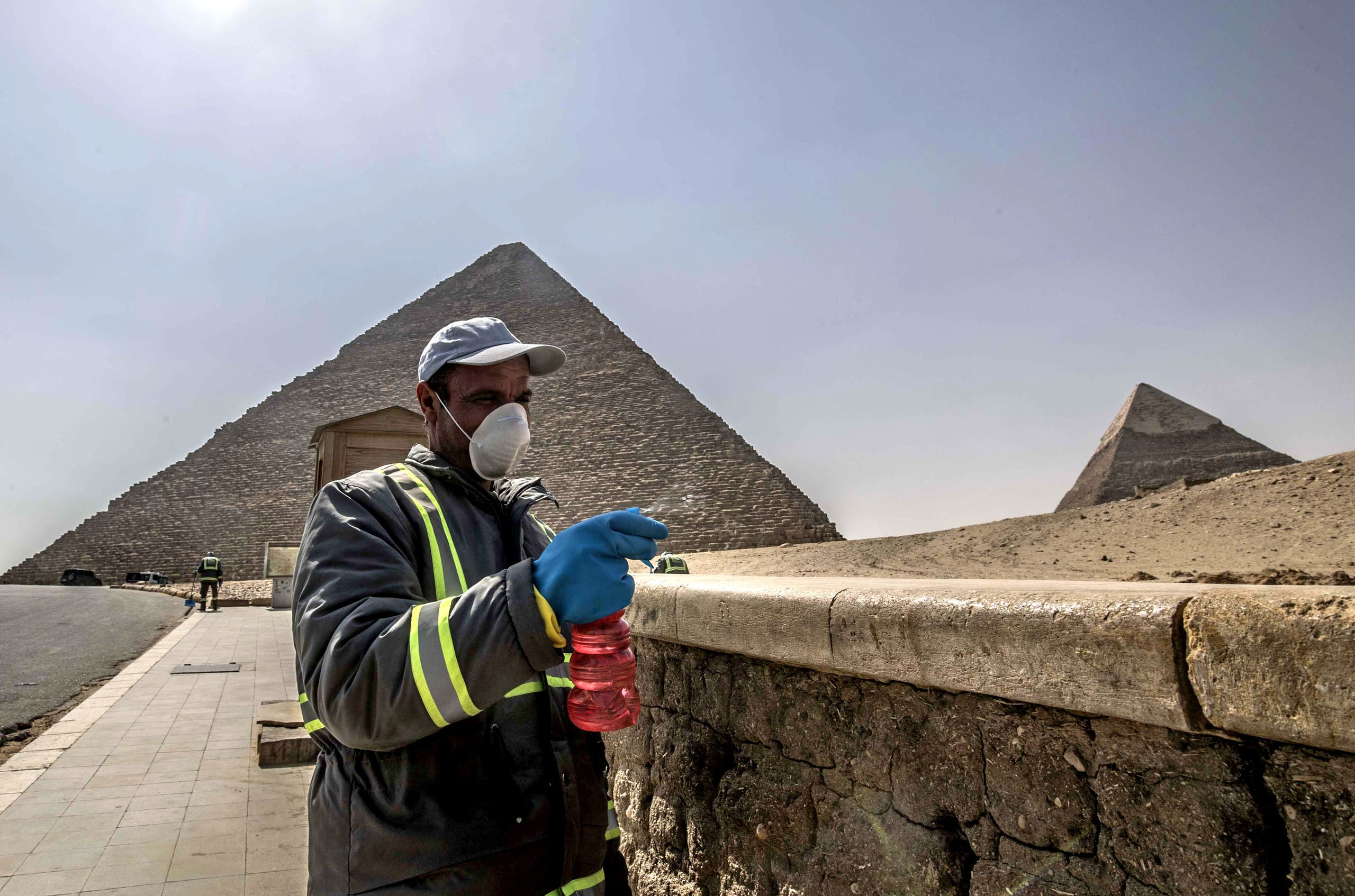 Egyptian municipality workers disinfect the Giza pyramids necropolis on the southwestern outskirts of the Egyptian capital Cairo on March 25, 2020 as protective a measure against the spread of the coronavirus COVID-19.(AFP)