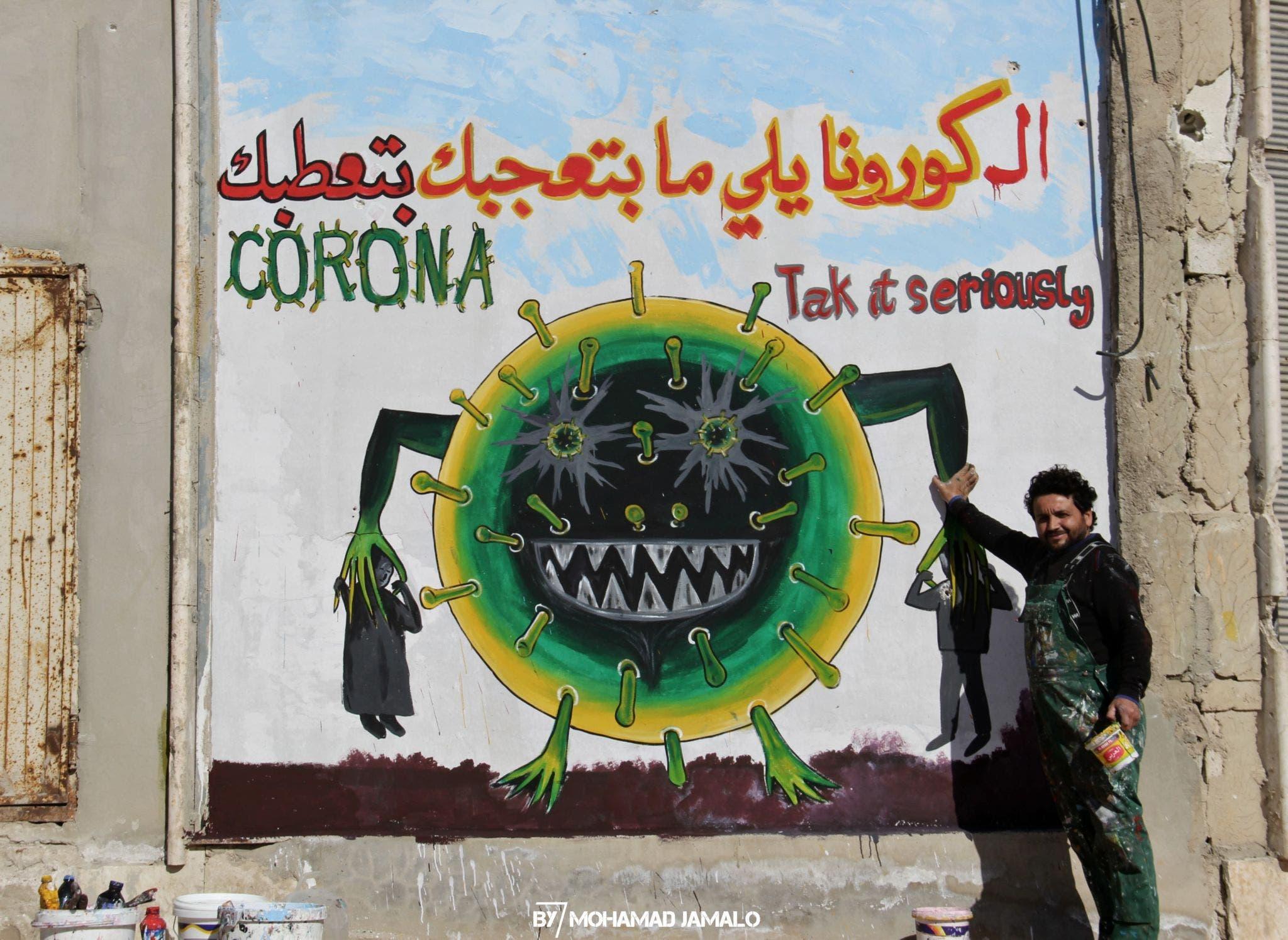 Syrian artist Aziz Asmar with a coronavirus mural in Idlib. (Mohamad Jamalo)