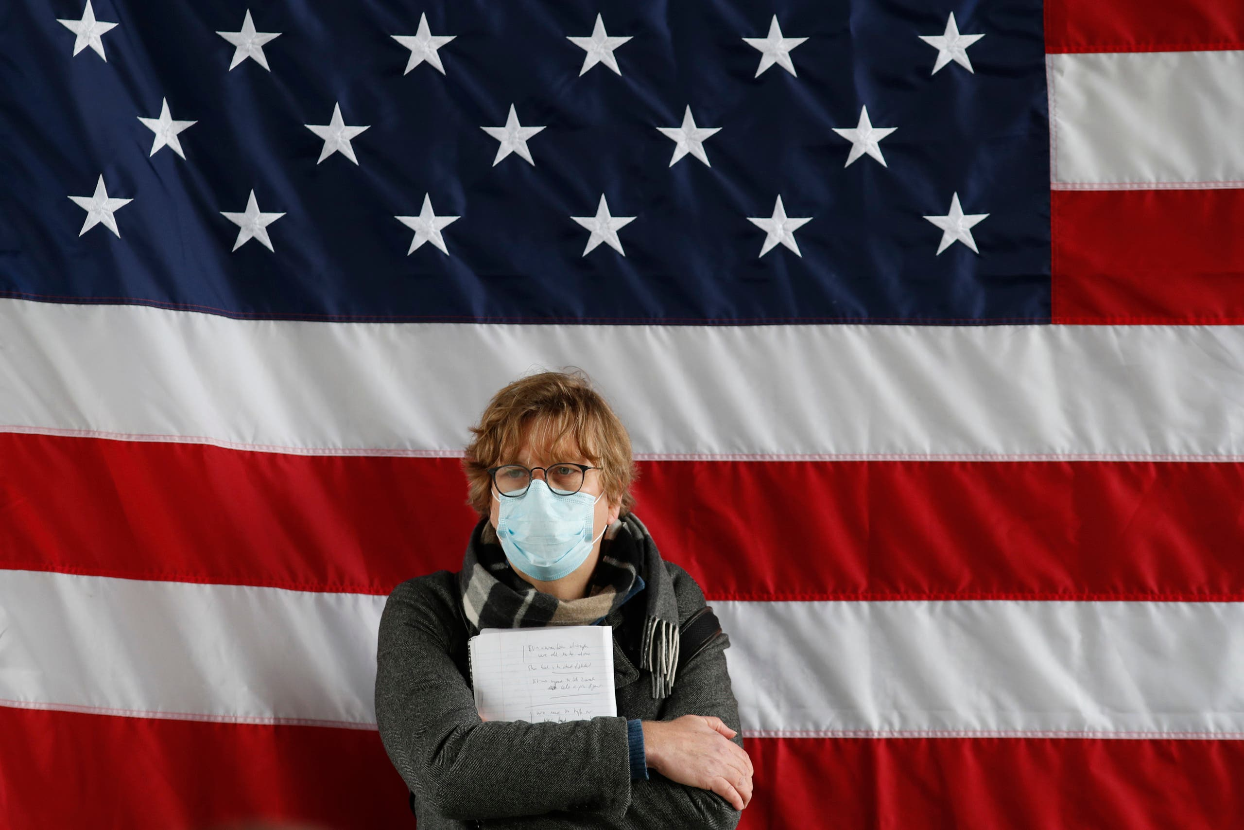 A reporter leans against the United States flag during a press briefing on March 30, 2020, in New York. (AP)