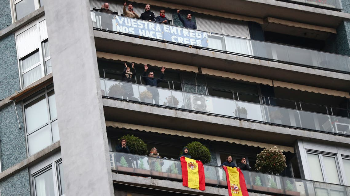 People confined in their homes applaud from their balconies in support of healthcare workers, outside Fundacion Jimenez Diaz hospital, amid the coronavirus disease (COVID-19) outbreak, in Madrid, Spain, March 30, 2020. Banner reads Your dedication makes us believe. REUTERS/Sergio Perez