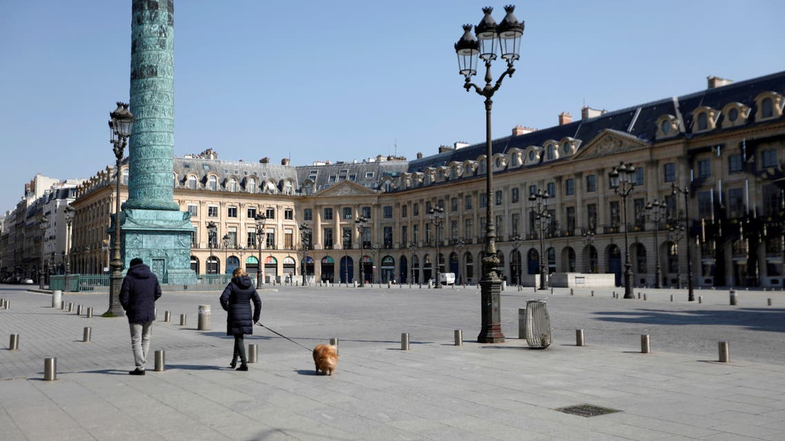 Local residents walk on the deserted Place Vendome in Paris as a lockdown is imposed to slow the rate of the coronavirus disease (COVID-19) in France, March 27, 2020. REUTERS/Charles Platiau