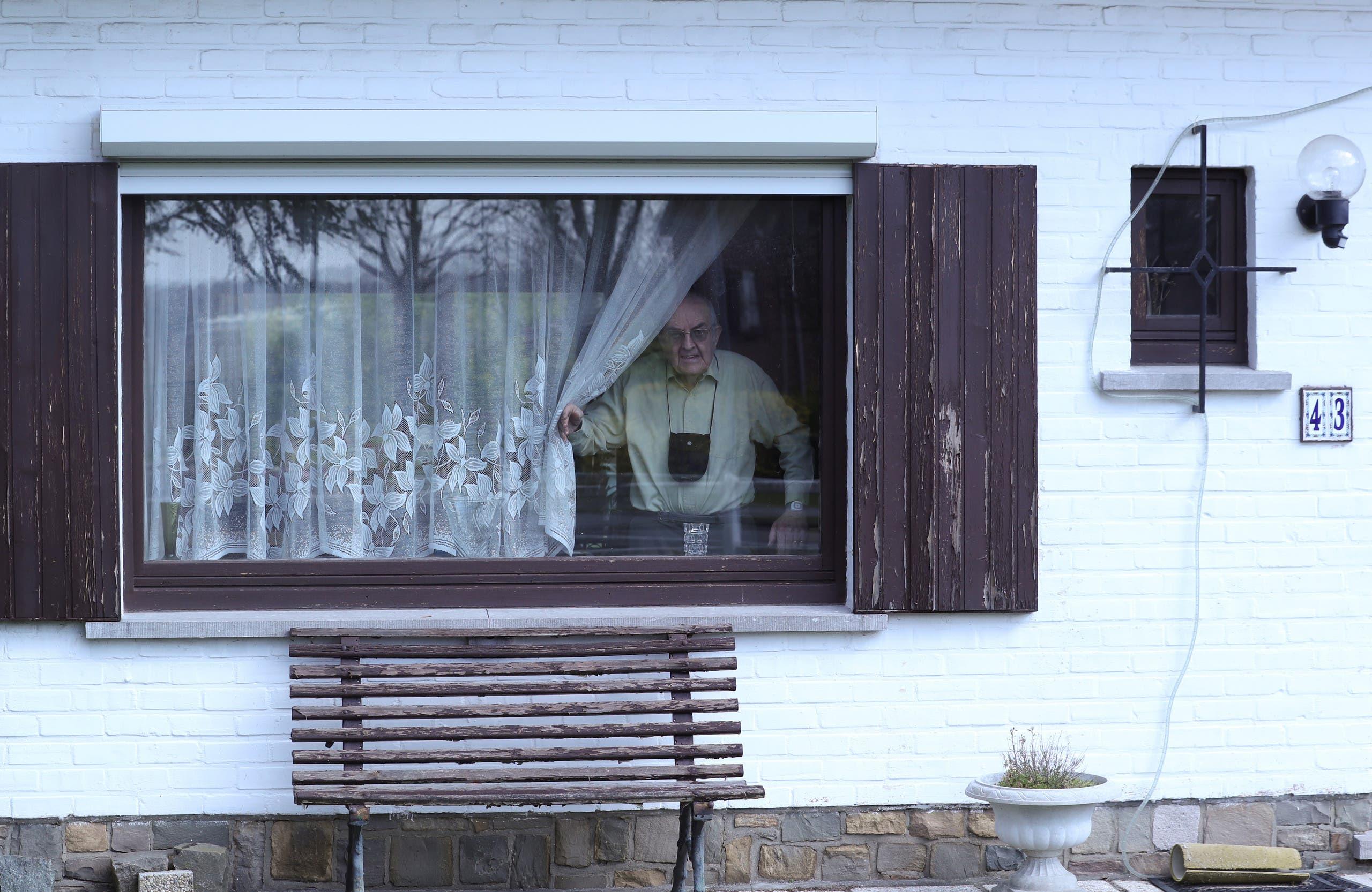 مسن بلجيكي يطل عبر نافذة منزله حيث يخضع للعزل في بروكسيل