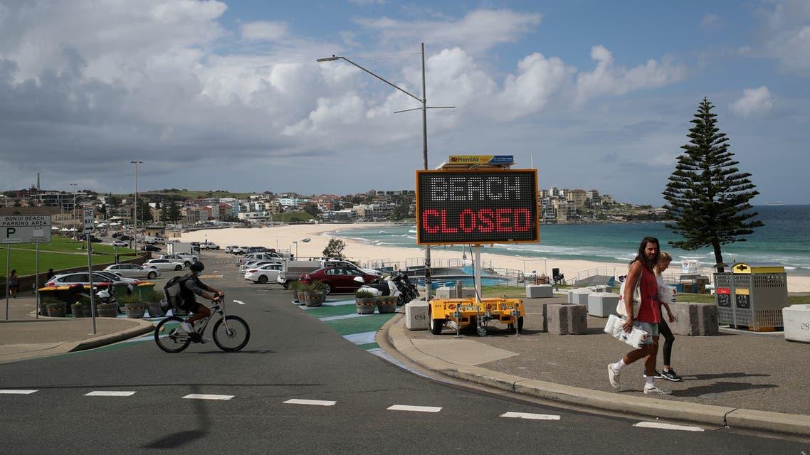 People walk past a Beach Closed sign at Bondi Beach, as the beach remains closed to prevent the spread of the coronavirus disease (COVID-19), in Sydney, Australia April 1, 2020. REUTERS/Loren Elliott
