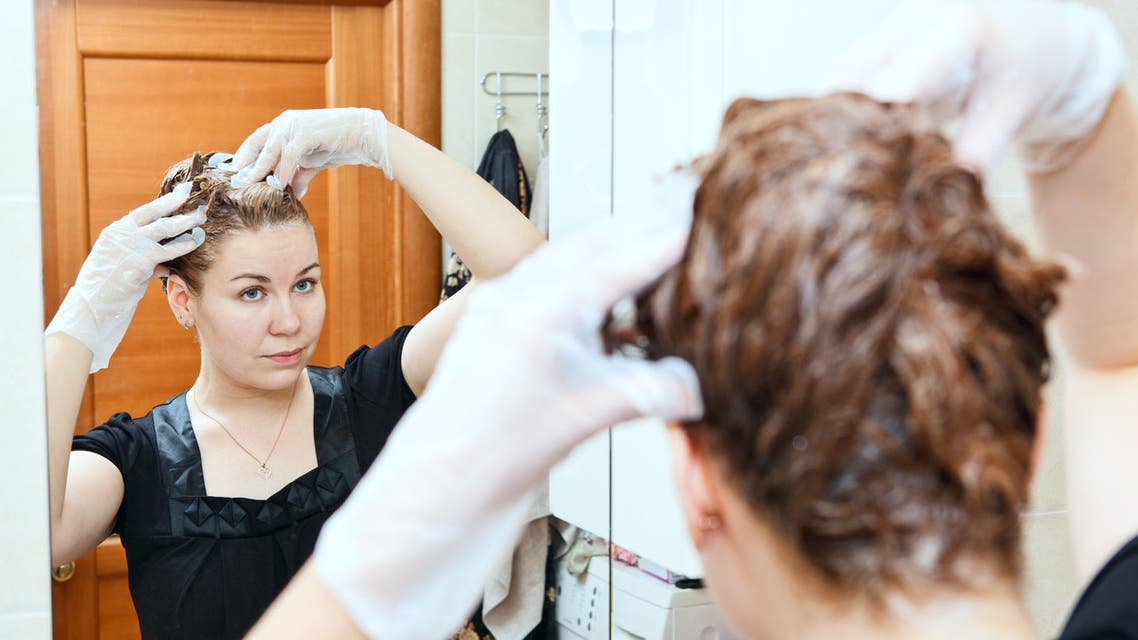 Woman dyeing hairs at home stock photo