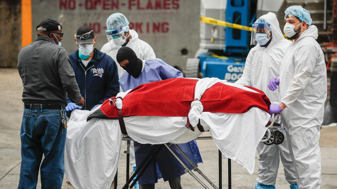 A body wrapped in plastic that was unloaded from a refrigerated truck is handled by medical workers wearing personal protective equipment. (AP)