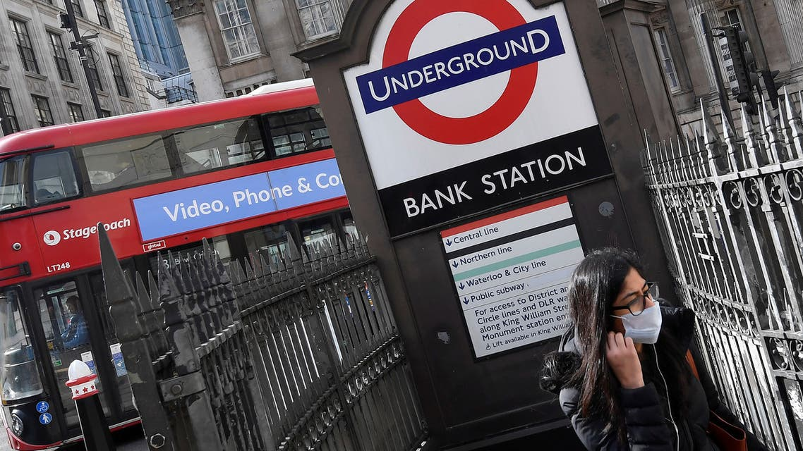 FILE PHOTO: A woman wearing a protective face mask walks out of an underground tube station in the City of London financial district, whilst British stocks tumble as investors fear that the coronavirus outbreak could stall the global economy, London, Britain, March 9, 2020. REUTERS/Toby Melville/File Photo