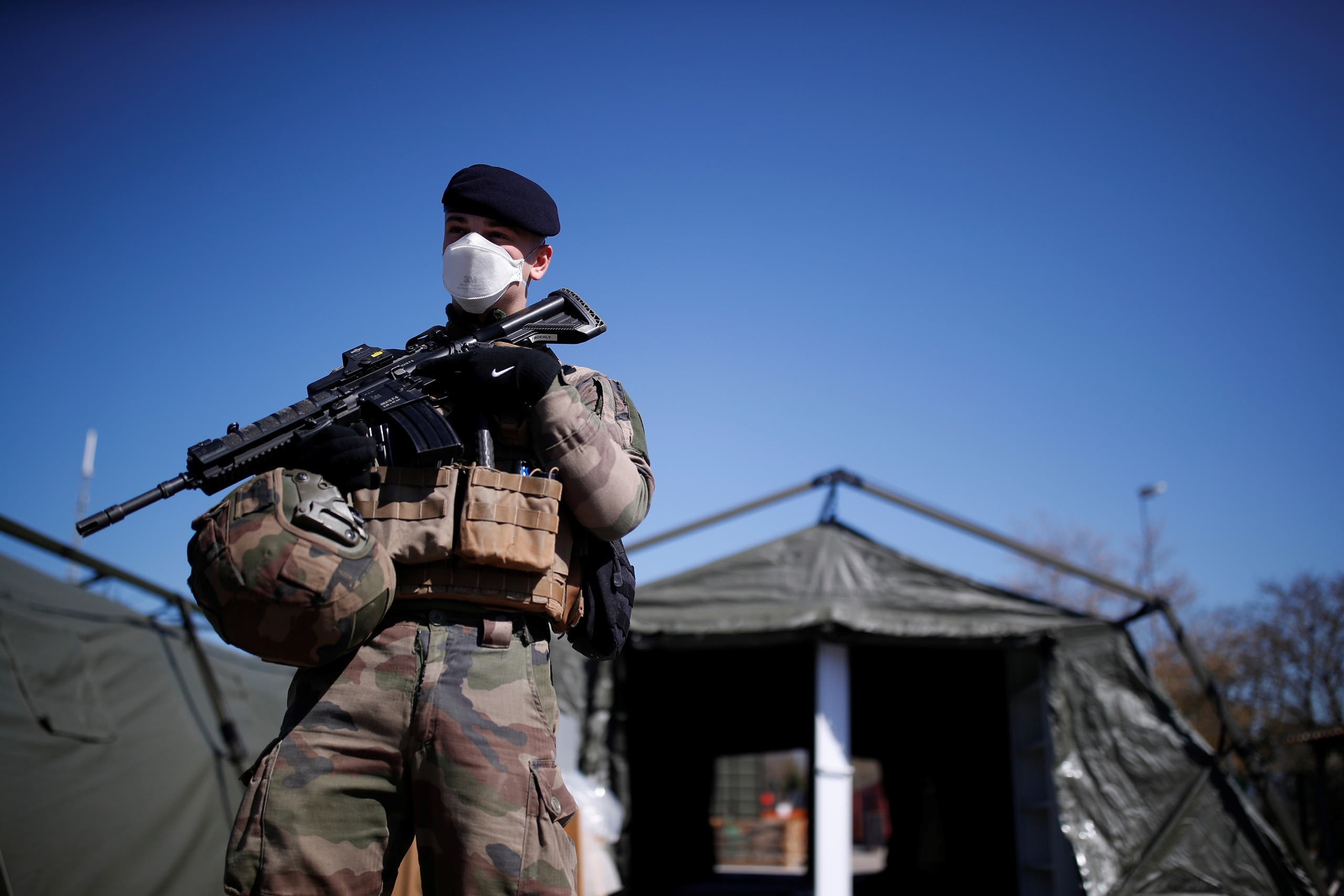 A French soldier, wearing a protective face mask, stands next to tents at a miitary field hospital near Mulhouse hospital as France faces an aggressive progression of the coronavirus disease (COVID-19), March 23, 2020. (Reuters)