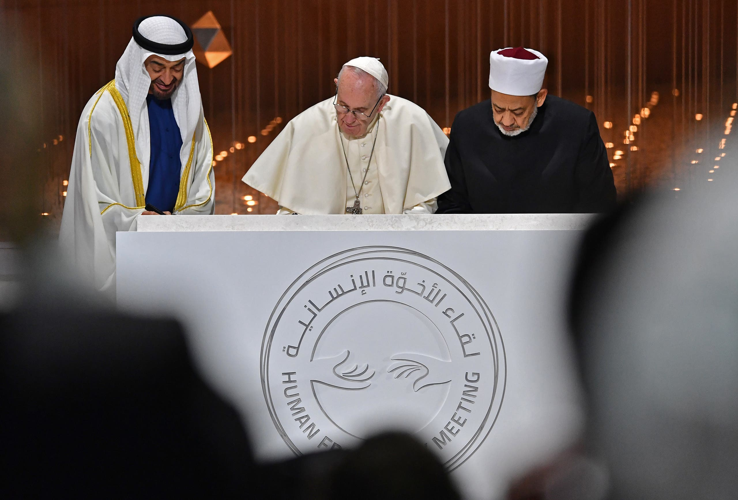 Abu Dhabi's Crown Prince Mohamed bin Zayed Al Nahyan (L) watches as Pope Francis (C) and Egypt's Azhar Grand Imam Sheikh Ahmed al-Tayeb sign documents during the Human Fraternity Meeting in Abu Dhabi on February 4, 2019. (AFP)