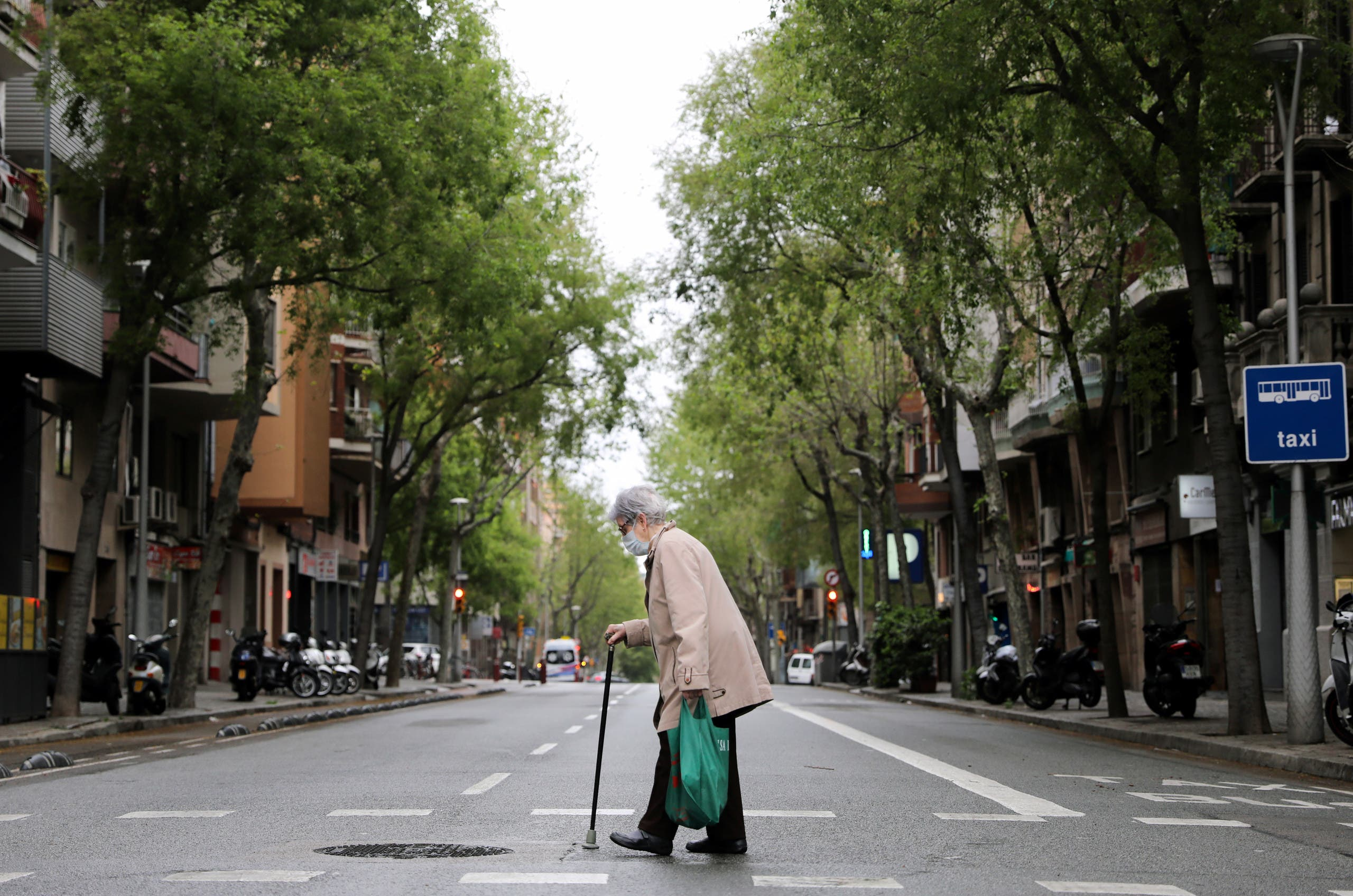 An elderly woman wears a protective face mask as she walks with shopping bags during the coronavirus disease (COVID-19) outbreak, in Barcelona, Spain April 1, 2020. (Reuters)