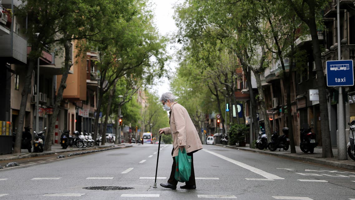 An elderly woman wears a protective face mask as she walks with shopping bags during the coronavirus disease (COVID-19) outbreak, in Barcelona, Spain April 1, 2020. REUTERS/Nacho Doce