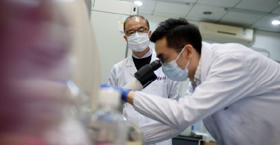 الخبير زانغ (واقفا) ينظر الى عالم آخر يدقق بالفيروس عبر المجهر
