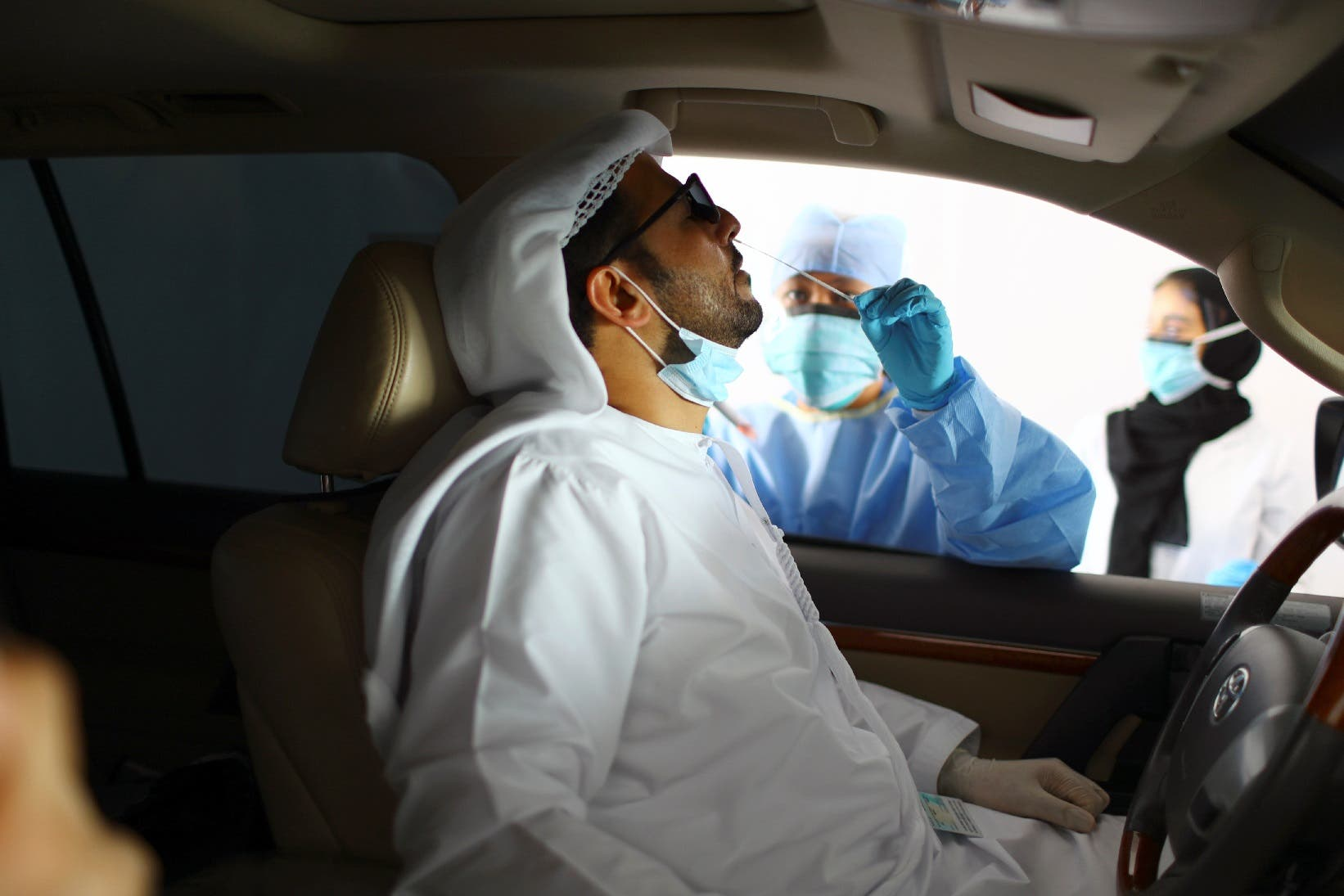 A member of medical staff wearing a protective face mask and gloves takes a swab from a man during drive-thru coronavirus testing at a screening center in Abu Dhabi, UAE. (File photo: Reuters)