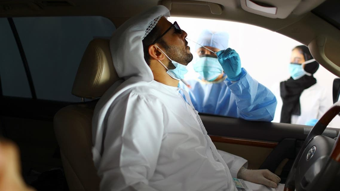 A member of medical staff wearing a protective face mask and gloves takes a swab from a man during drive-thru coronavirus disease testing (COVID-19) at a screening center in Abu Dhabi, United Arab Emirates, March 30, 2020. (Reuters)