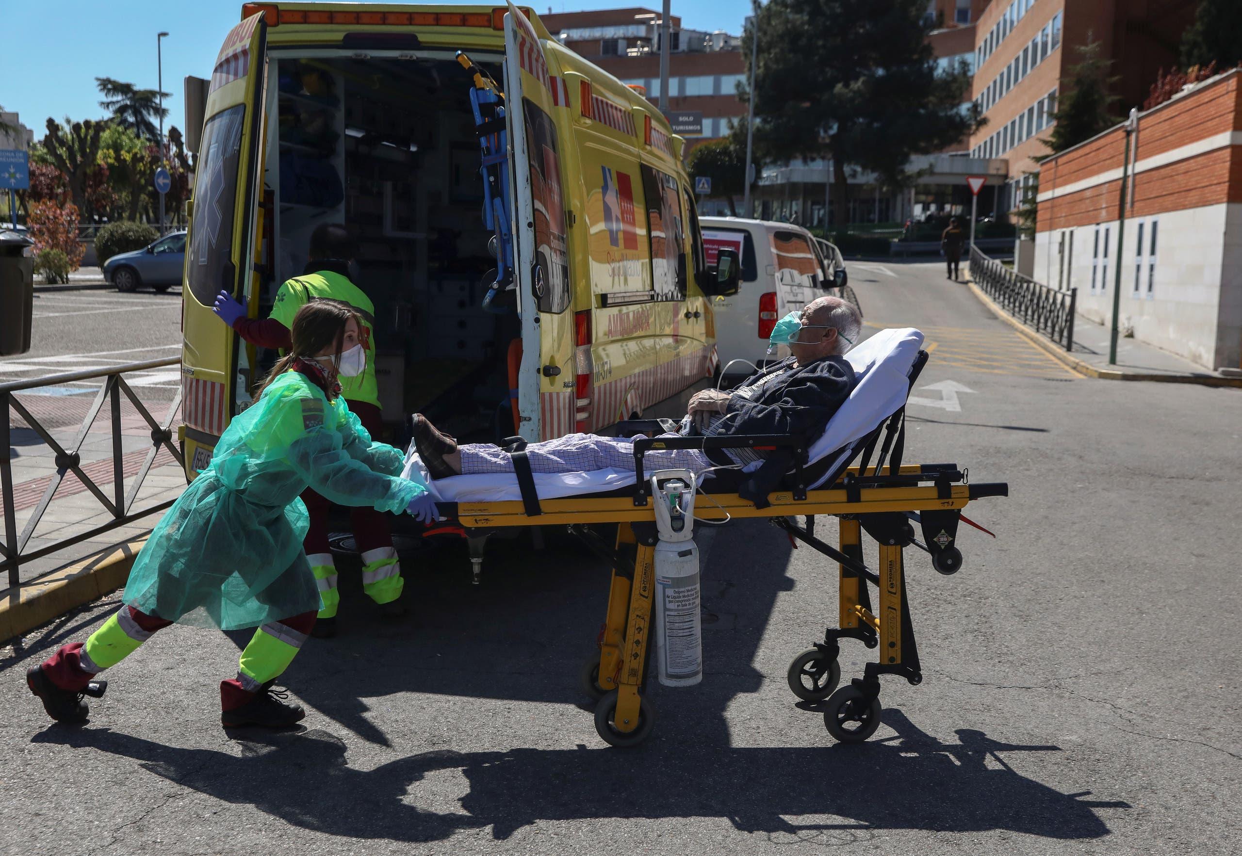 موظفة رعاية صحية تدفع مريضاً على سرير متحرك إلى وحدة الطوارئ بمستشفى في مدريد يوم 28 مارس (رويترز)