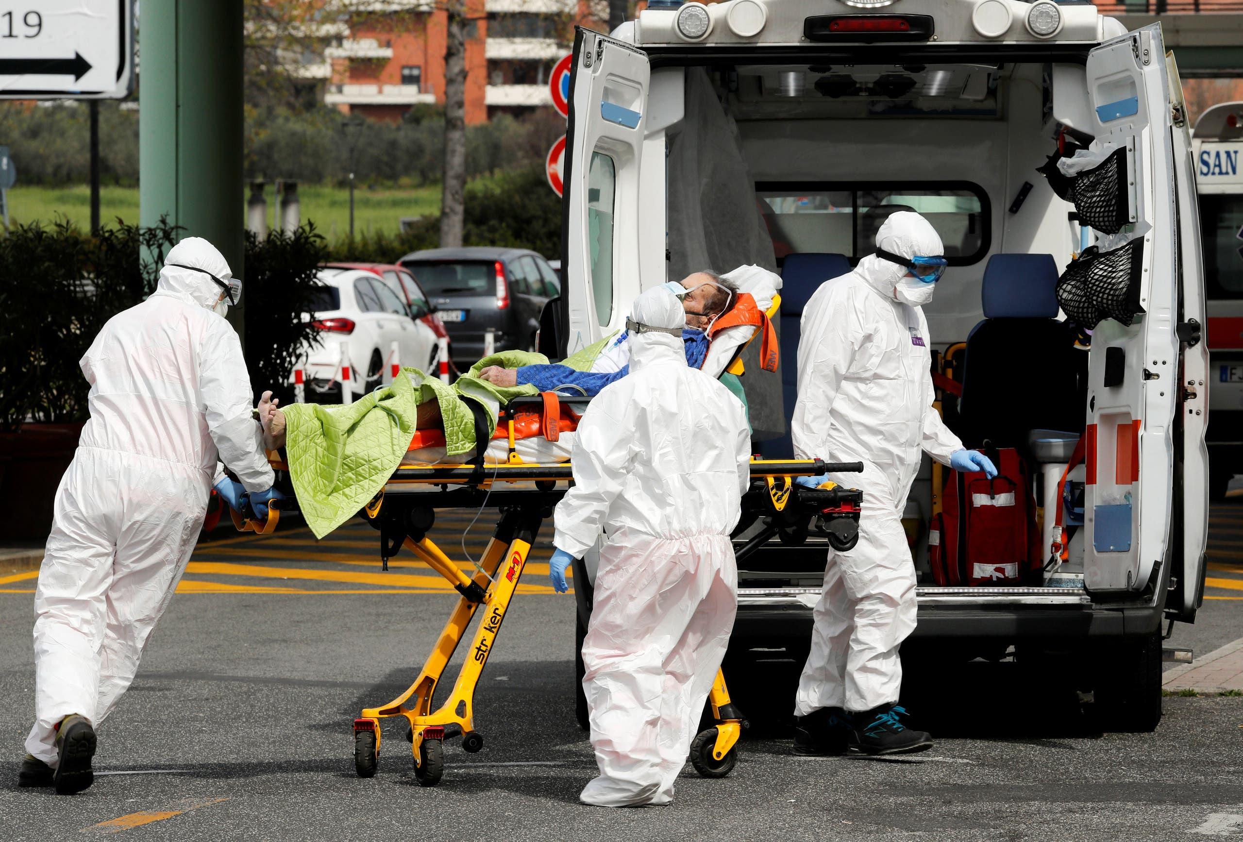أفراد بالرعاية الصحية ينقلون مريضاً بفيروس كورونا في روما يوم 30 مارس (رويترز)