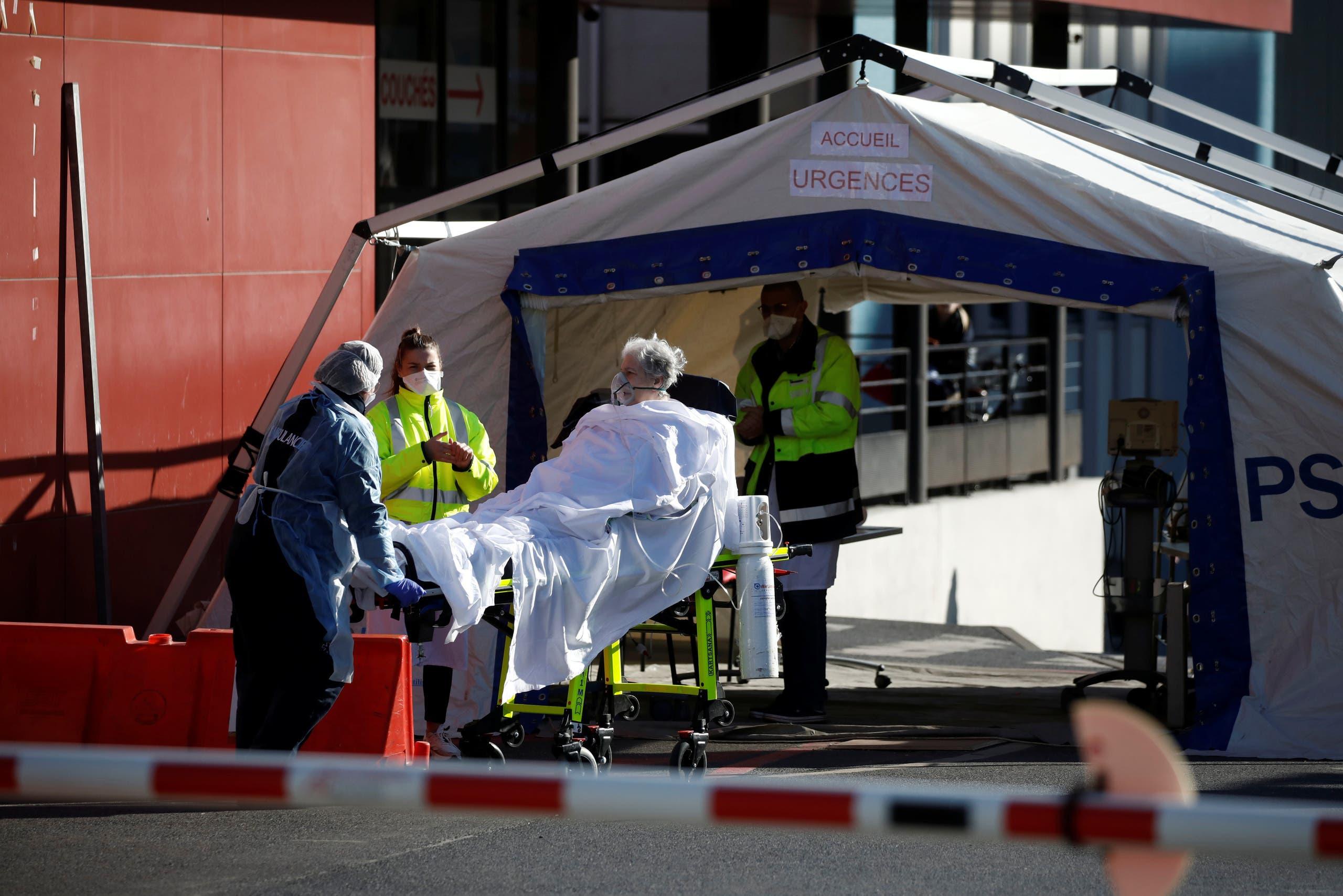 مسعفون ينقلون مريضاً بفيروس كورونا من سيارة إسعاف إلى مستشفى بالقرب من باريس يوم 30 مارس (رويترز)