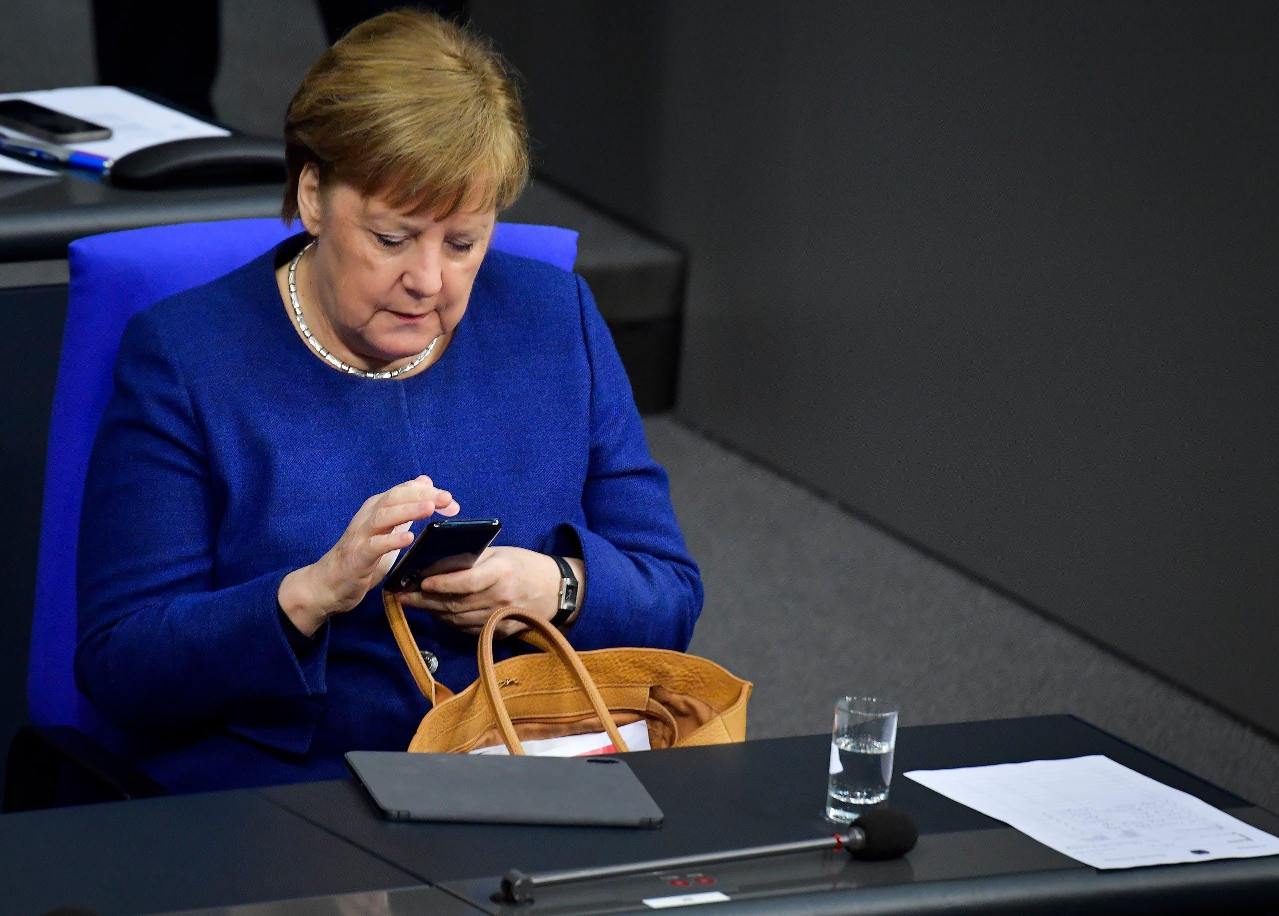 أنجيلا ميركل تنظر إلى هاتفها المحمول(أرشيفية- فرانس برس)