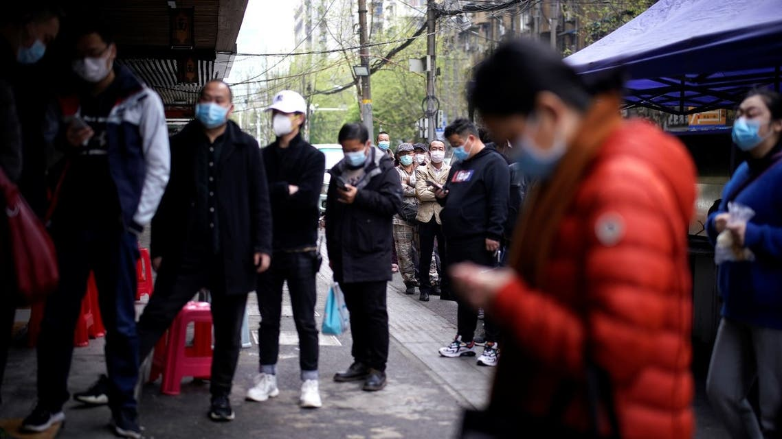 People wearing face masks line up to pay for their breakfast, at a residential area blocked by barriers in Wuhan, Hubei province, the epicentre of China's coronavirus disease (COVID-19) outbreak, April 2, 2020. (Reuters)