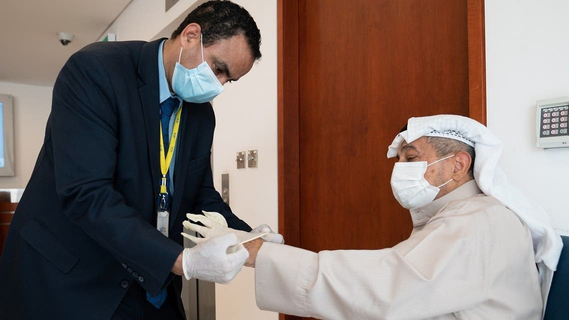 A bank security guard helps an elderly client put protective gloves on before he enters the bank, following the outbreak of coronavirus, in Shaab, Kuwait March 15,2020. (Reuters)