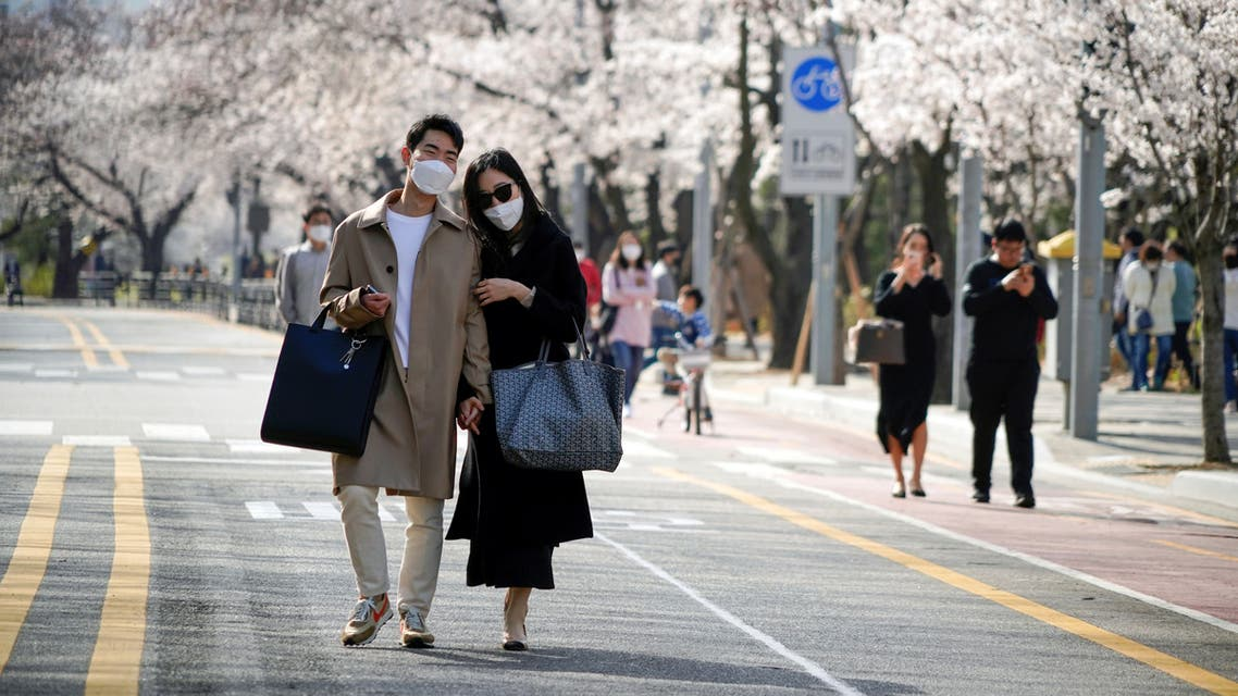 A couple takes a walk near a cherry blossom trees street, closed to avoid the spread of the coronavirus disease (COVID-19), in Seoul, South Korea. (Reuters)