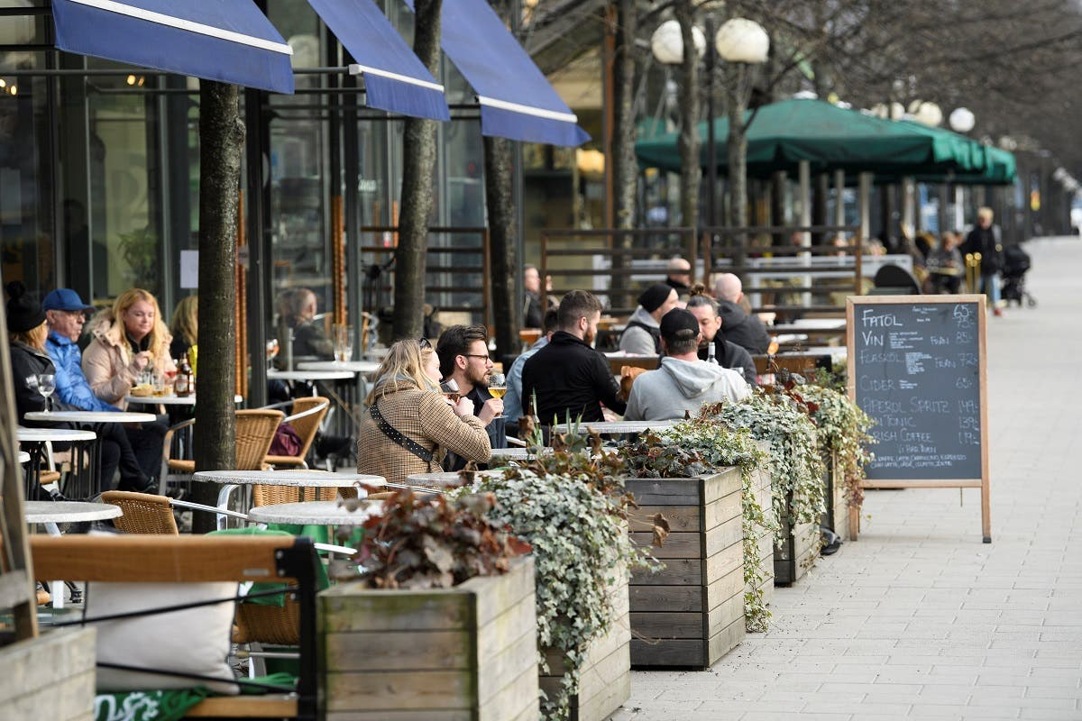 People sit at an outdoor restaurant in Kungstradgarden park amid the new coronavirus spread, in Stockholm, Sweden March 27, 2020. (Reuters)