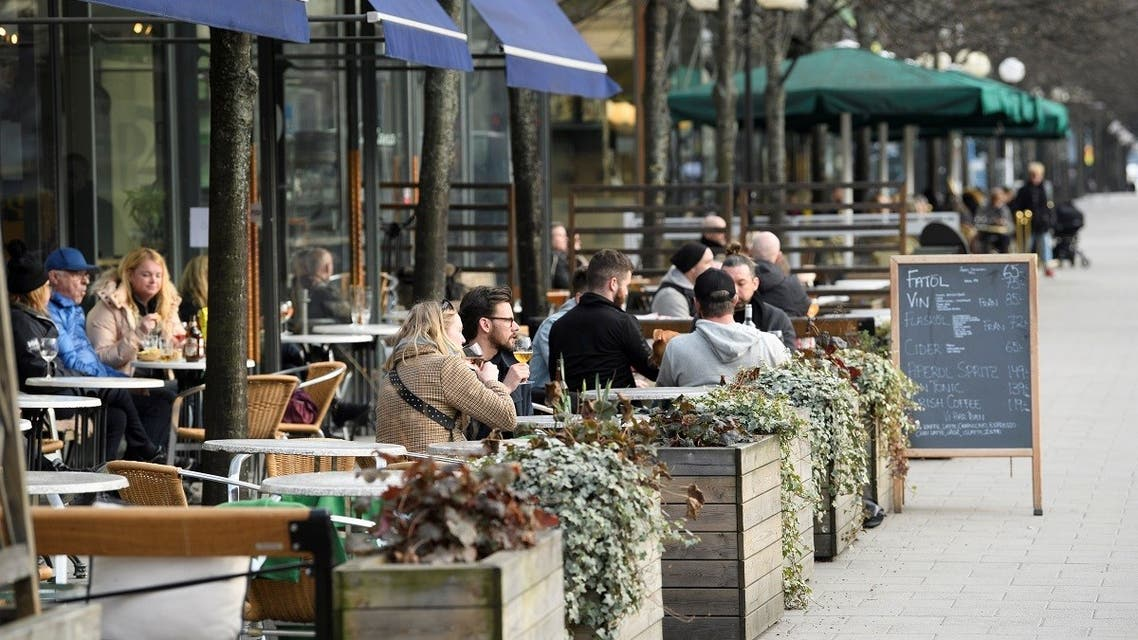 People sit at an outdoor restaurant in Kungstradgarden park amid the new coronavirus (COVID-19) spread, in Stockholm, Sweden March 27, 2020. (Reuters)