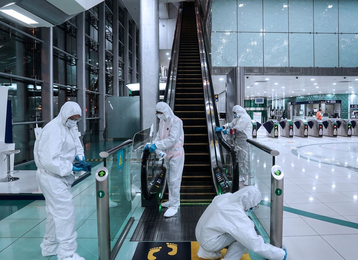 Members of a medical team wearing protective suits clean an escalator, after a curfew was imposed to prevent the spread of the coronavirus disease (COVID-19), in Dubai. (Reuters)